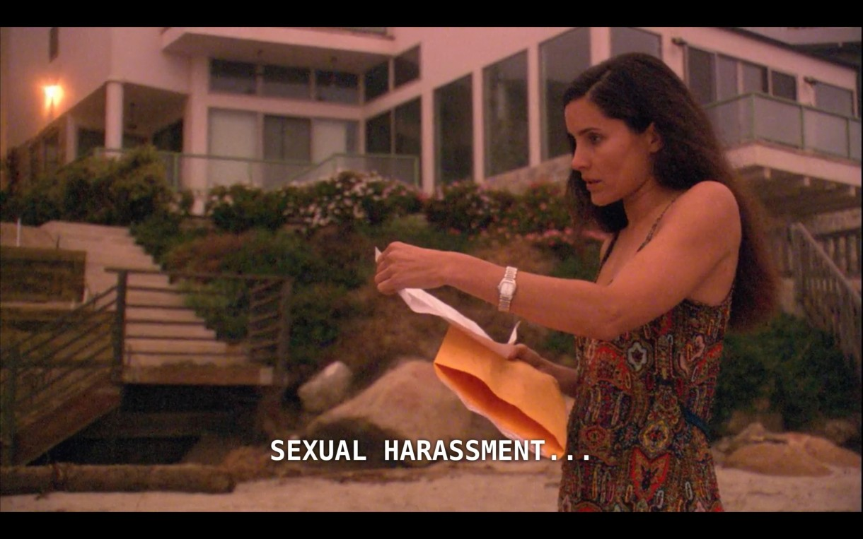 """Helena stands on the beach in front of her mansion. She has just opened an envelope delivered to her, looks at the paper, and says, """"Sexual harassment..."""""""