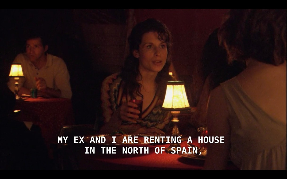 """A dimly lit restaurant in which Alice is on a date with a woman with long wavy hair and wearing a v-neck dress. Alice's date tells her, """"My ex and I are renting a house in the north of Spain"""""""