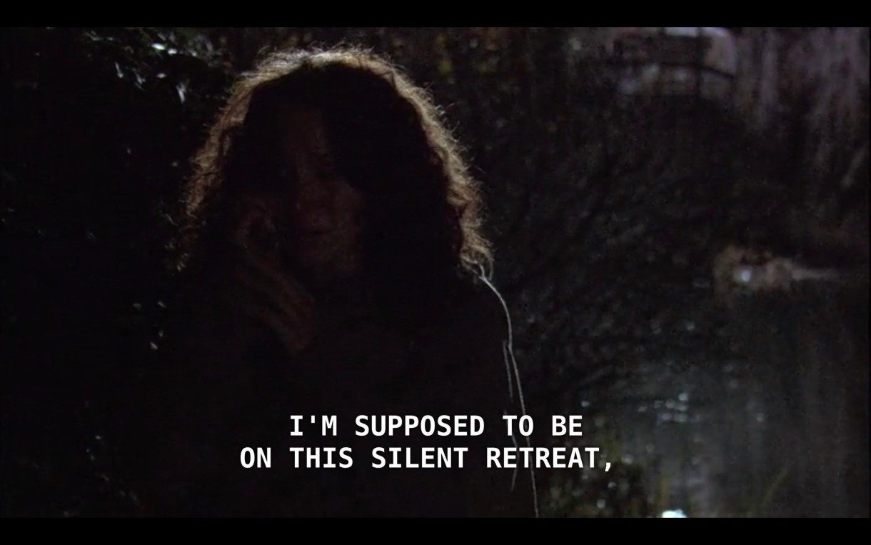 """Bette is calling Tina on her cell phone in a dark forest at night. She says, """"I'm supposed to be on this silent retreat."""""""