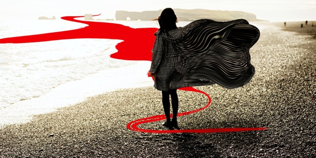 woman standing at edge of water with cape flying and a swirl of red around her