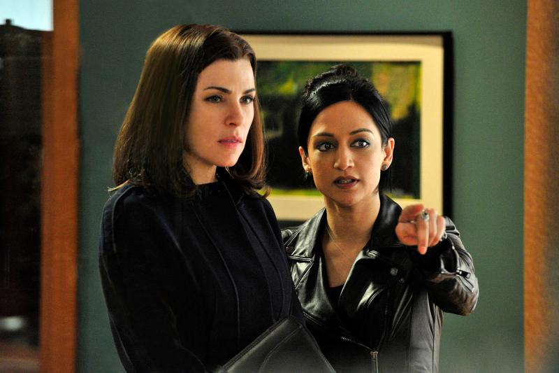 Image: Alicia Florrick, played by Juliana Marguiles, is wearing a black shirt and cardigan and holding a legal brief. She is standing next to Kalinda Sharma, played by Archie Panjabi, who is wearing a black leather jacket and pointing towards the camera. Alicia is looking in the direction that Kalinda is pointing. Behind them is a green wall with a painting hanging on it.