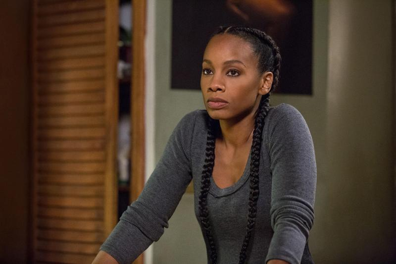 Black woman with two braids and a long sleeve grey shirt stands in a room with her hands on the counter, looking slightly annoyed