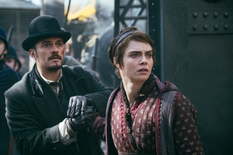 Image: A man in a hat with facial hair stands next to Cara Delevingne, who has short hair like an elf and a headband