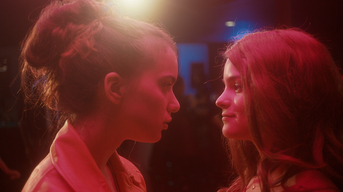Two young women, bathed in pink-red light, stare at each other full of hope and love. This is a lesbian movie available for streaming on Hulu.