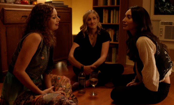 three women in a dark living room with a bottle between them
