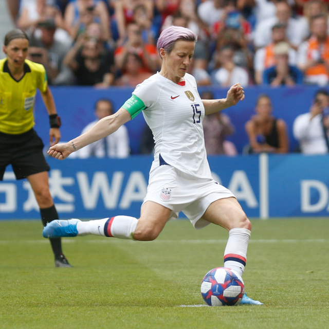 Soccer player Megan Rapinoe kicks a soccer ball