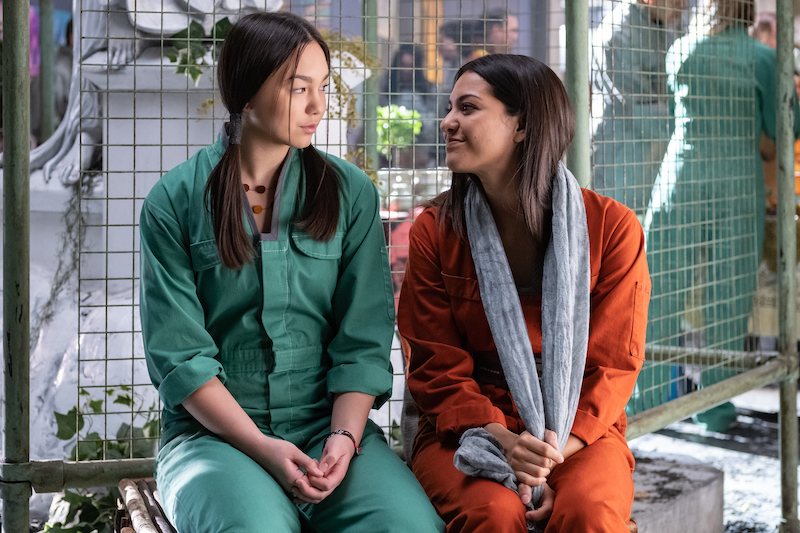 Image: two girls in Utopia Falls are sitting next to each other, one in a green jumpsuit, the other in an orange jumpsuit with a grey scarf around her neck.