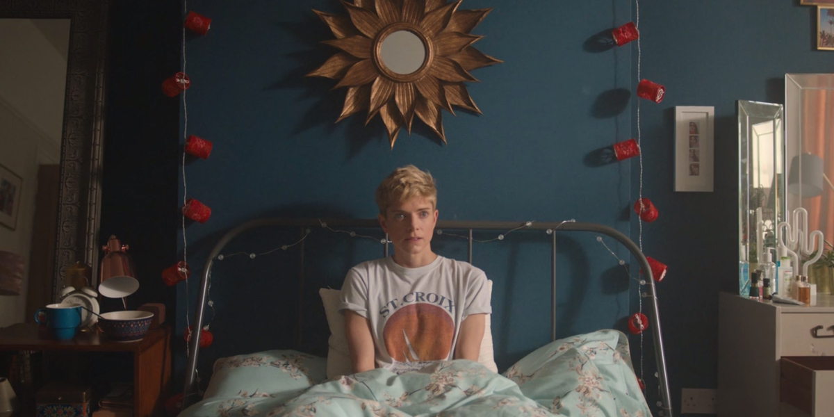 """Mae Martin in """"Feel Good."""" Mae Martin is sitting in her bed, in front of a blue wall"""