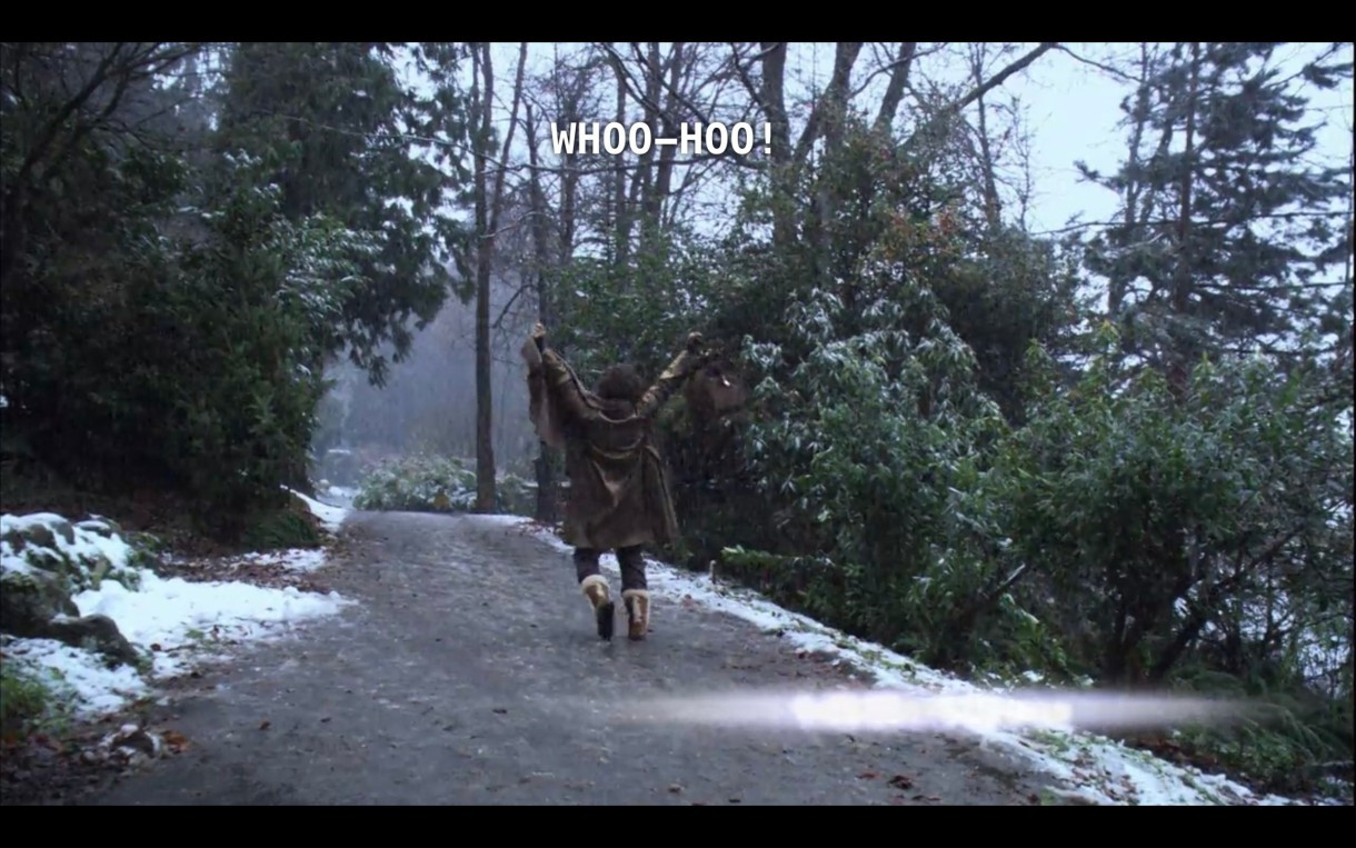 """Bette, with her back to the camera, is walking down a dirt path in the woods, with a light dusting of snow. She raises both arms in the air and yells, """"Whoo-hoo!"""" as she leaves her silent retreat."""