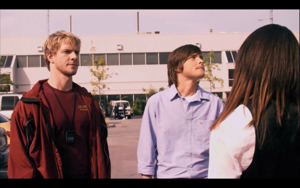 Tim (wearing a red t-shirt under a red track jacket) stands next to Max (wearing a blue button-up) and opposite of Jenny (whose back is to the camera) in a parking lot. Tim is looking blankly at Jenny, and Max is looking embarrassed and off into the distance.