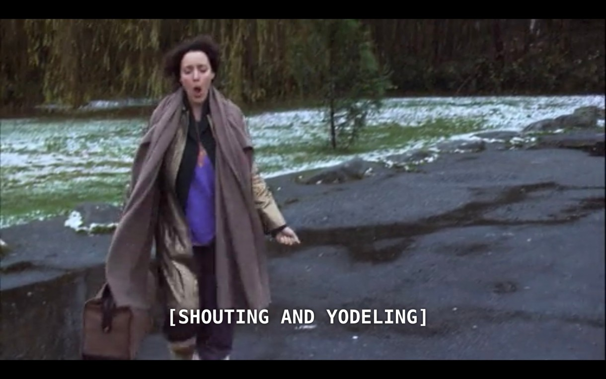 """Bette (wearing a purple shirt under a long brown jacket) is carrying a duffle bag as she walks happily down a lightly snowy road as she continues to leave her silent retreat. The subtitles show that she is """"[shouting and yodeling]"""""""