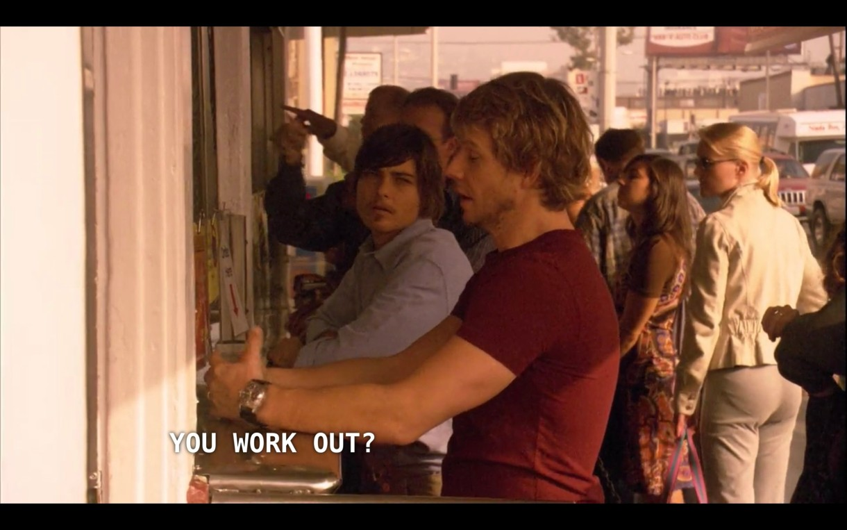 """Tim (wearing a red t-shirt) and Max (wearing a blue button-up) stand at an outdoor bar. Max asks, """"You work out?"""""""
