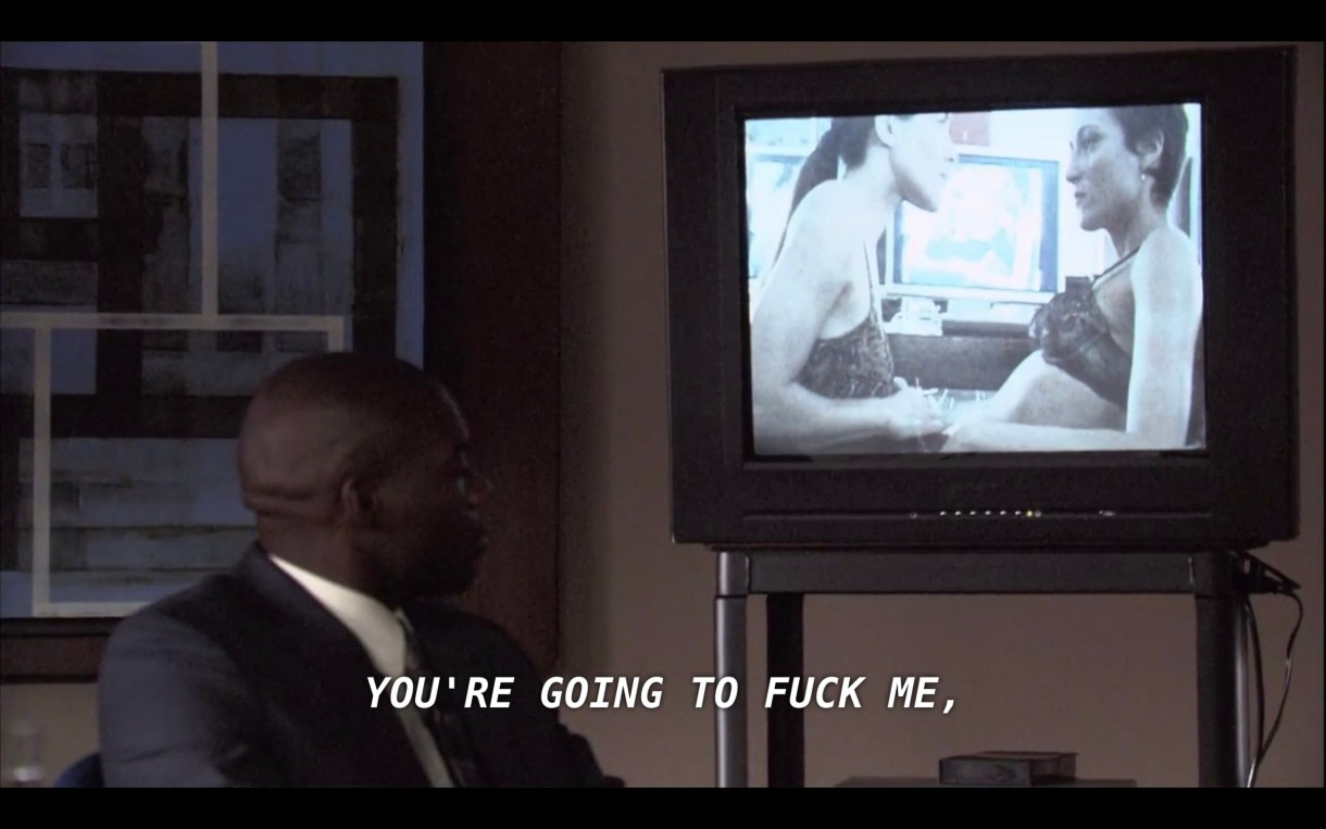 """A bald man in a full suit looks back over his shoulder at an old chunky TV on a rolly cart. On the TV is a blurry video of Helena and Dylan in their bras. Through the TV Helena says, """"You're going to fuck me."""""""