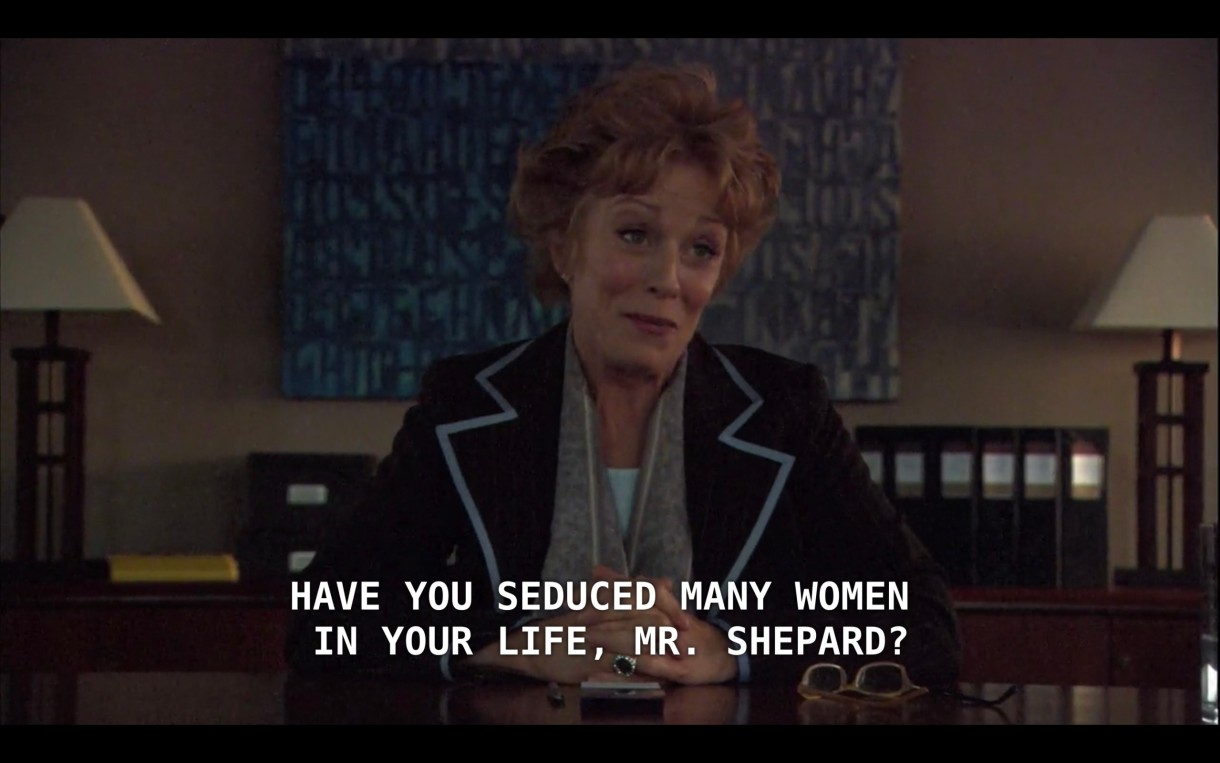 """Peggy Peabody sits at the head of a board room table, wearing a black blazer. She says to Dylan's lawyer, """"Have you seduced many women in your life, Mr. Shepard?"""""""