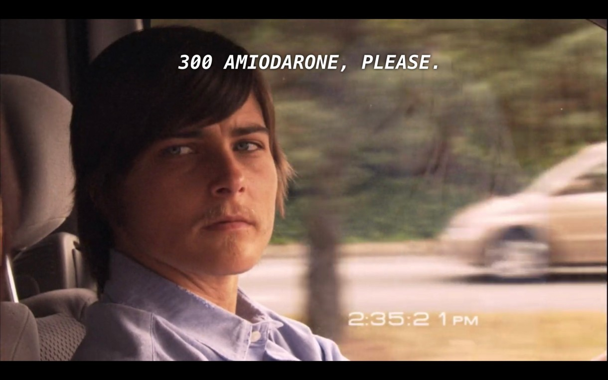 """Max (wearing a blue button-up) is driving and looks over seriously at Jenny (off camera). The subtitles read, """"300 Amiodarone, please,"""" referring to what is happening in Dana's hospital room at that moment."""""""