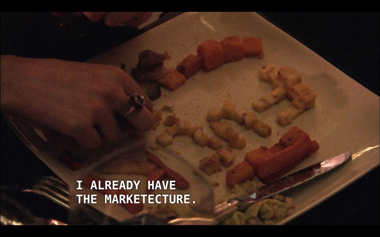 """A white square dinner plate featuring tiny carrots and potatoes. Just in frame, Jenny's hand is spelling out """"FUC"""" in tiny potatoes. Off screen, Max's boss's wife says, """"I already have the marketecture."""""""