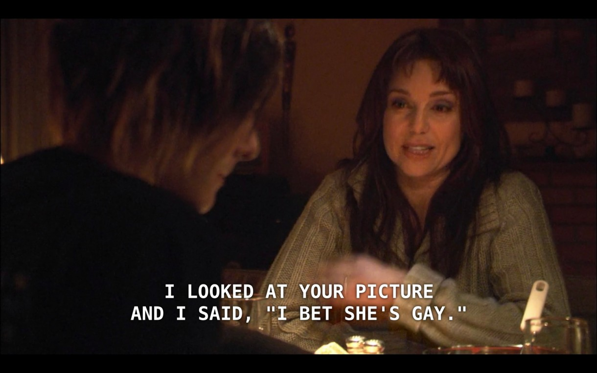 """Shane (wearing a black jacket, her back to the camera) sits across the table from her step-mom (wearing a gray sweater.) Shane's step-mom says, """"I looked at your picture and I said, 'I bet she's gay.'"""""""
