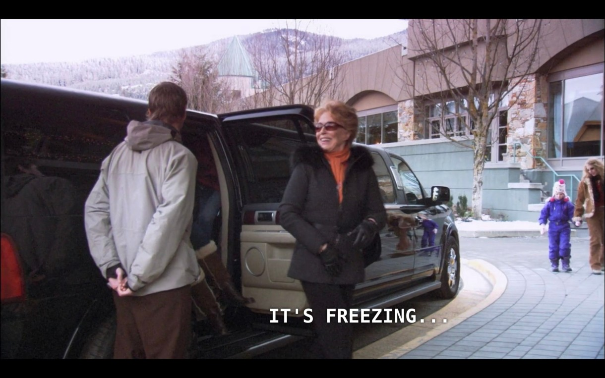 """Peggy Peabody (wearing an orange sweater under a black fur-lined coat and black gloves) steps out of a stretch limo. She says, """"It's freezing..."""""""