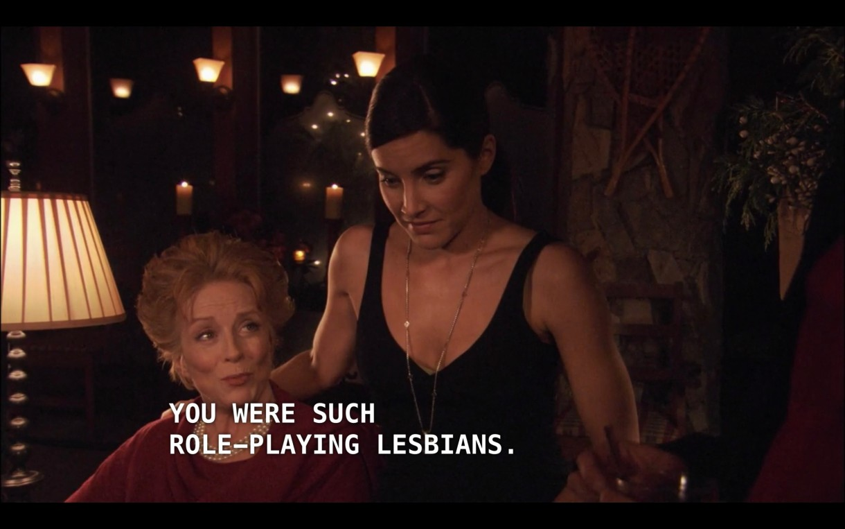 """Peggy Peabody is wearing a red sweater and sitting at a table in a dimly lit room. Helena (wearing a black dress and a long gold necklace) has her hand on her mom's shoulder. Peggy says, """"Oh my goodness, I had no idea you were such role-playing lesbians."""""""