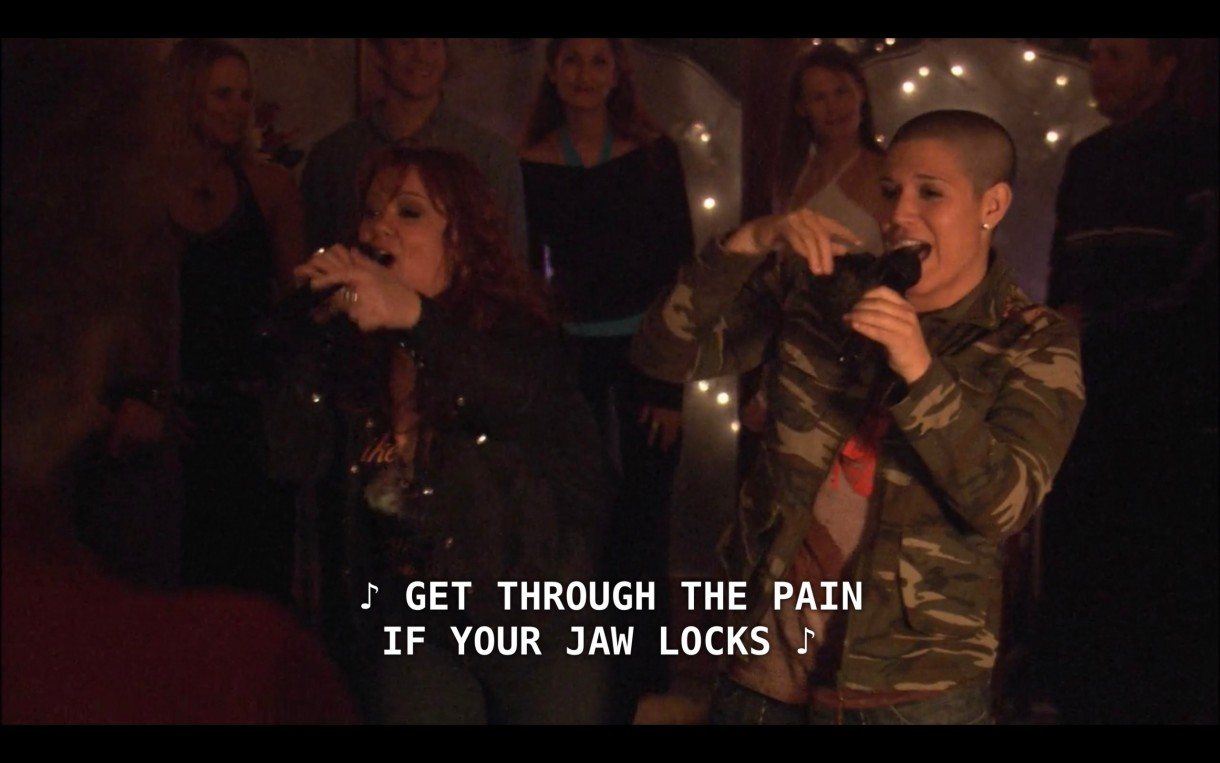 """Famed singers, God-des (who has a shaved head and is wearing a camouflage jacket) and She (who has curly red hair and wearing a black jacket), sing, """"Get through the pain if your jaw locks."""""""