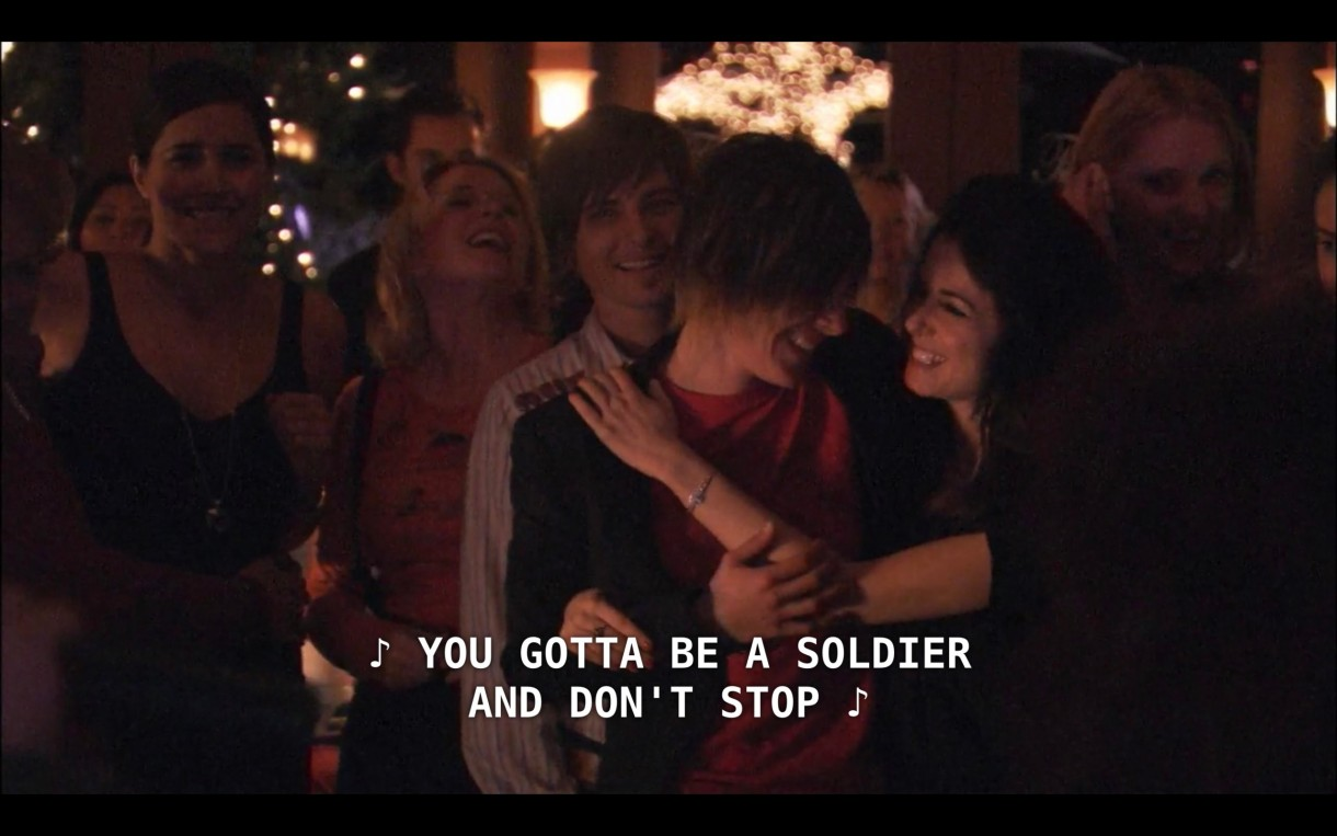 """A group of Helena, Tina, Max, Shane, and Jenny laugh and watch God-des and She continue their performance. Off camera, they sing, """"You gotta be a soldier and don't stop."""""""