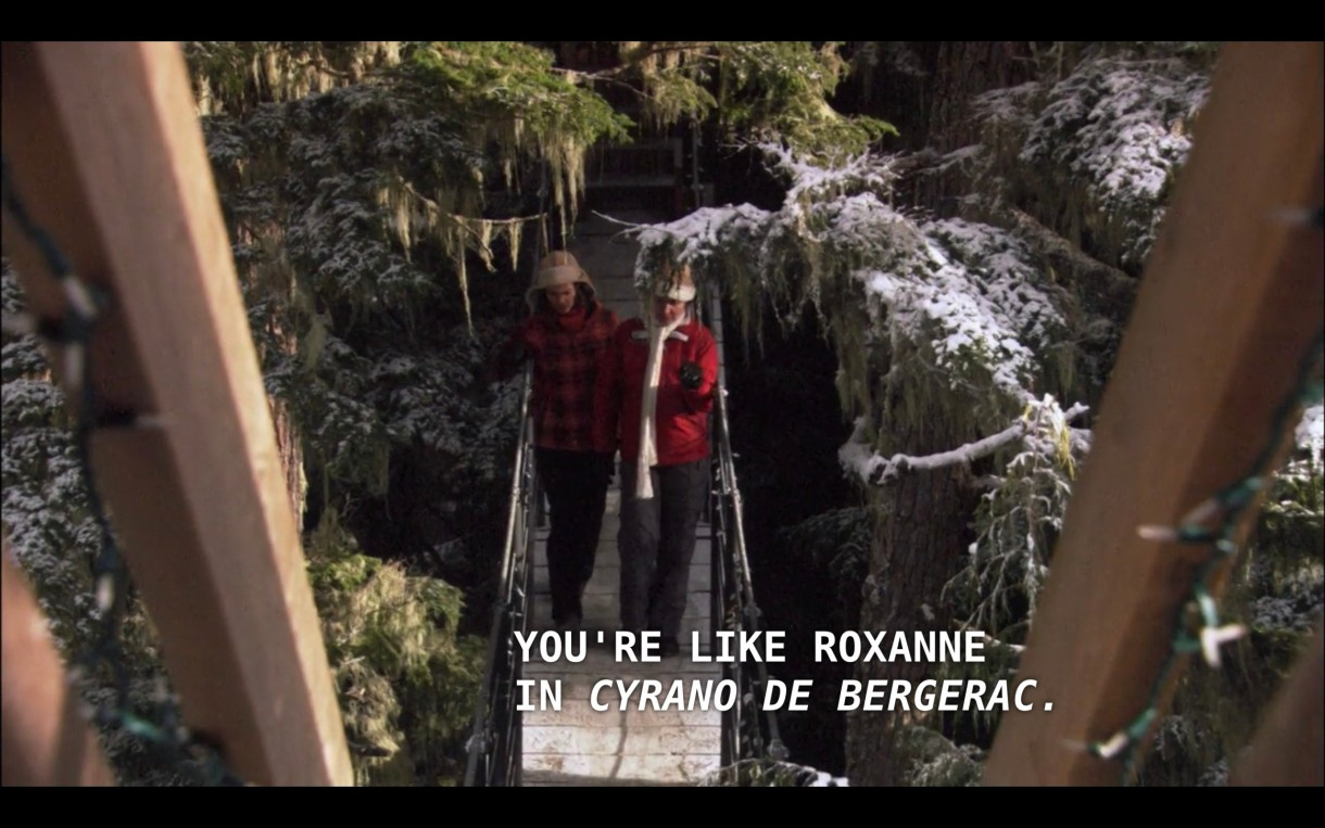"""Alice (wearing a red plaid winter jacket and a brown ear-flap hat) walks next to Marilyn (a woman Alice just met, wearing a red winter jacket and white scarf) walk across a wooden bridge amongst snow-covered evergreen trees. Marilyn says, """"You're like Roxanne in 'Cyrano de Bergerac.'"""""""