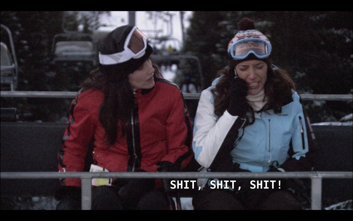 """Helena (wearing a red ski jacket, black hat, and ski goggles) and Bette (wearing a blue and white ski jacket, hat, and goggles) on a chairlift. Bette is listening to her voicemail and says, """"Shit, shit, shit!"""""""