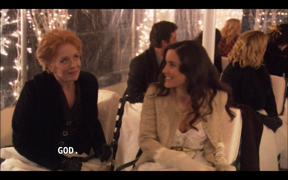 """Peggy (wearing a black jacket) and Helena (wearing a white top under a tan jacket) sit in tent for Carmen and Shane's wedding. Tina and Henry, and other guest, are sitting behind them. Peggy says, """"God."""""""