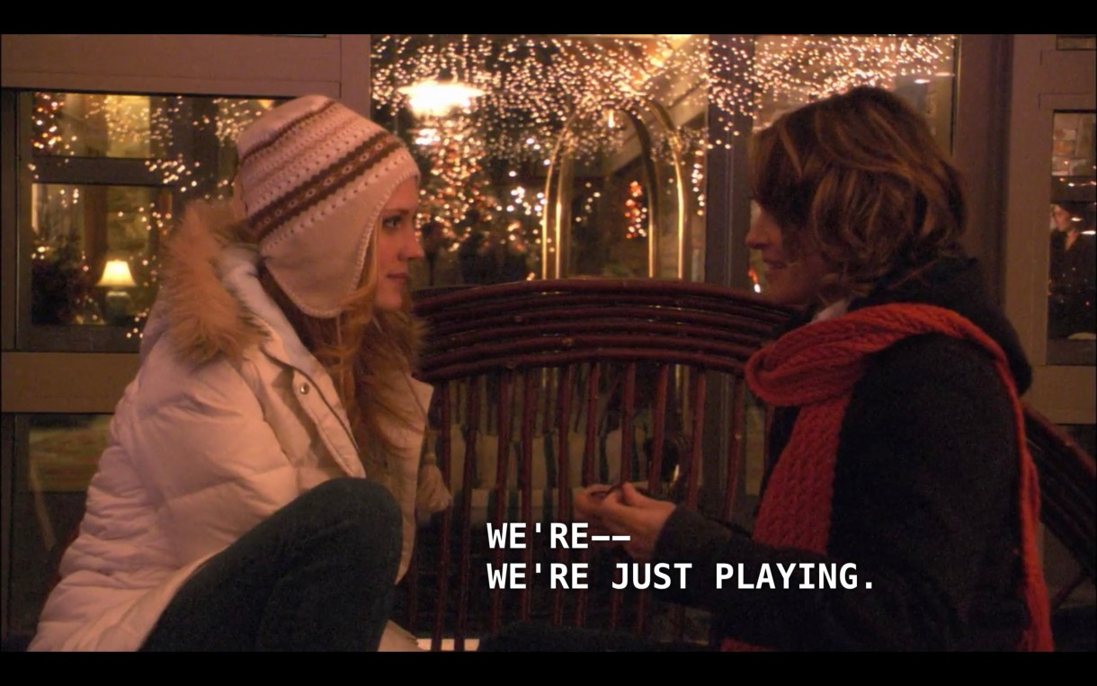 """Lara (wearing a white puffy coat and a tan hat) and Alice (wearing a black jacket and red scarf) sit on a bench in front of a big room with tons of twinkly lights hanging from the ceiling. Alice says, """"We're -- we're just playing."""""""