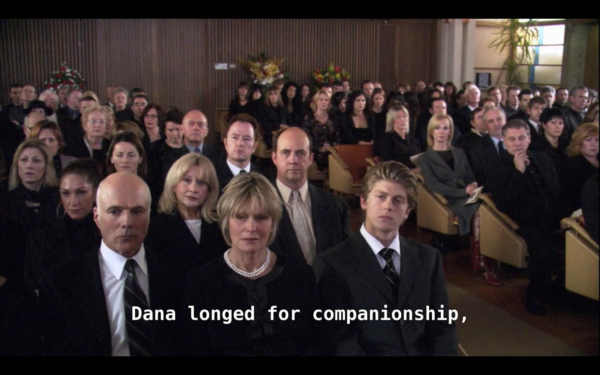 """A crowd of people dressed in all black attending Dana's funeral service. The minister (off camera) says, """"Dana longed for companionship."""""""