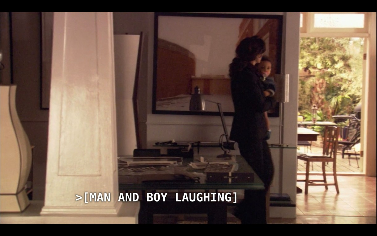 """Bette (wearing a black pantsuit) is carrying Angelica through her house. The subtitles say, """"[Man and boy laughing]"""""""