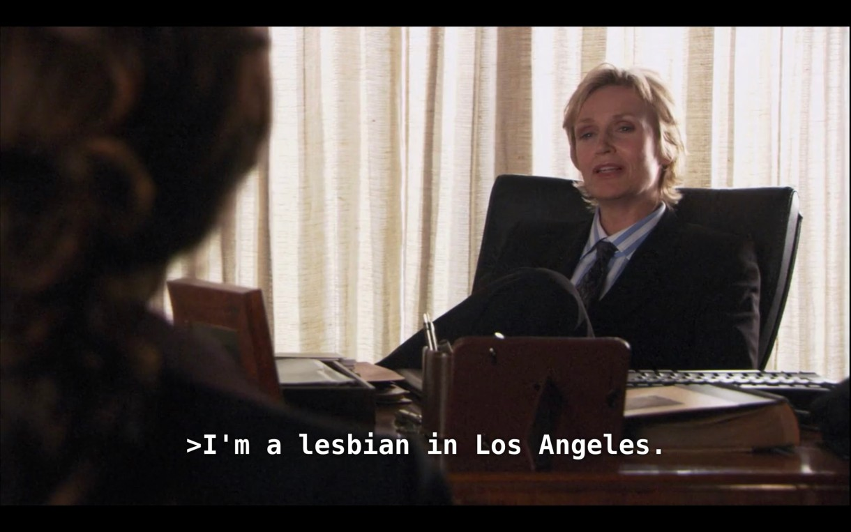 """Joyce (the lesbian lawyer played by Jane Lynch) is sitting behind her desk and wearing a black blazer over a blue-and-white shirt and a tie. She says to Bette (who is sitting across from her, her back to the camera), """"I'm a lesbian in Los Angeles."""""""