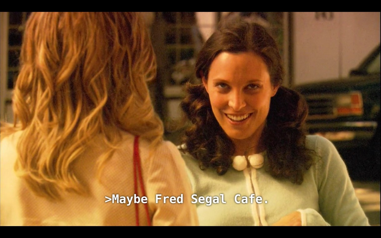 """Dana (wearing pig tails and a light blue sweater) is looking at Alice (wearing a pink sweater, her back to the camera) with a sly look on her face. Dana says, """"Maybe Fred Segal Cafe"""""""
