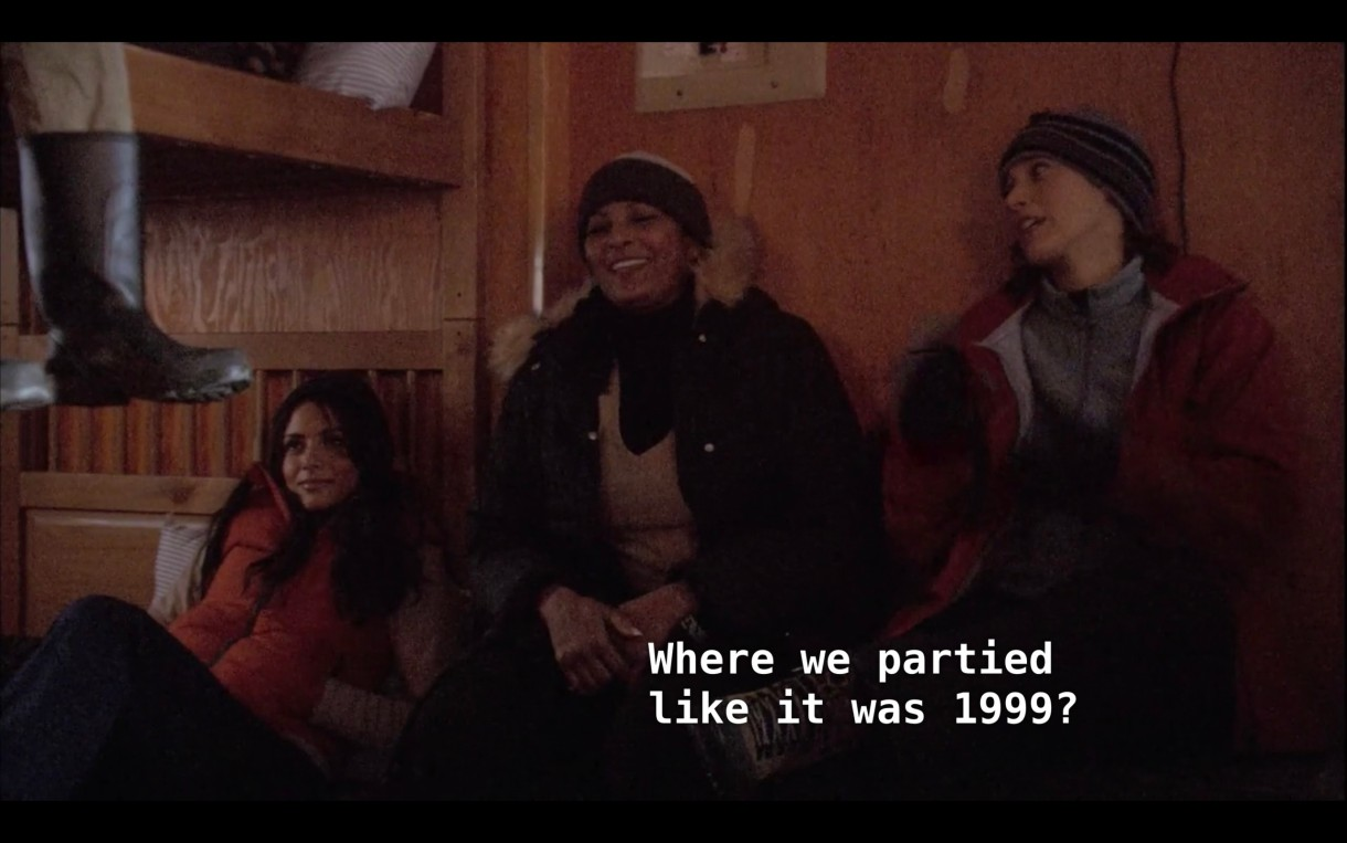 """Carmen (wearing an orange puffy vest), Kit (wearing a fur lined black jacket), and Bette (wearing a red jacket) sit next to each other in a cabin. Kit asks, """"Where we partied like it was 1999?"""""""