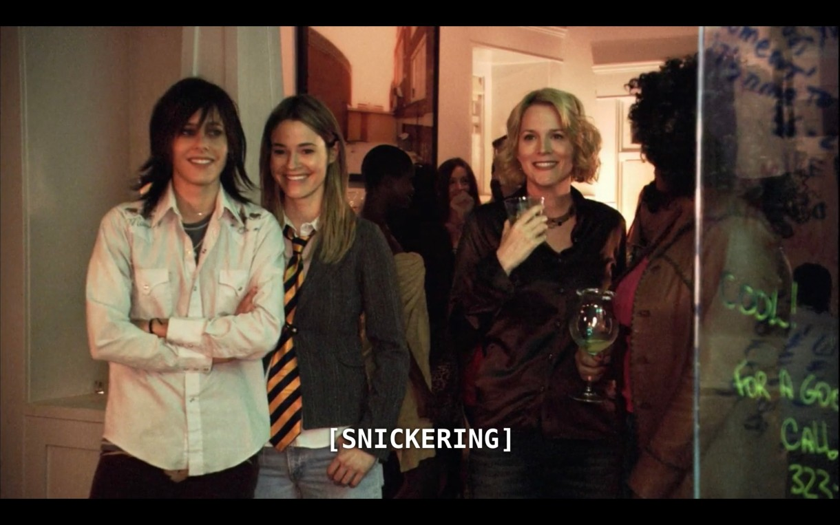 """A flashback scene in which Shane (wearing a white button-up), Alice (wearing a grey sweater and black-and-yellow striped neck tie) and Tina (wearing a dark brown blouse and holding a cocktail glass) are standing at a party. The subtitles say, """"[Snickering]"""""""