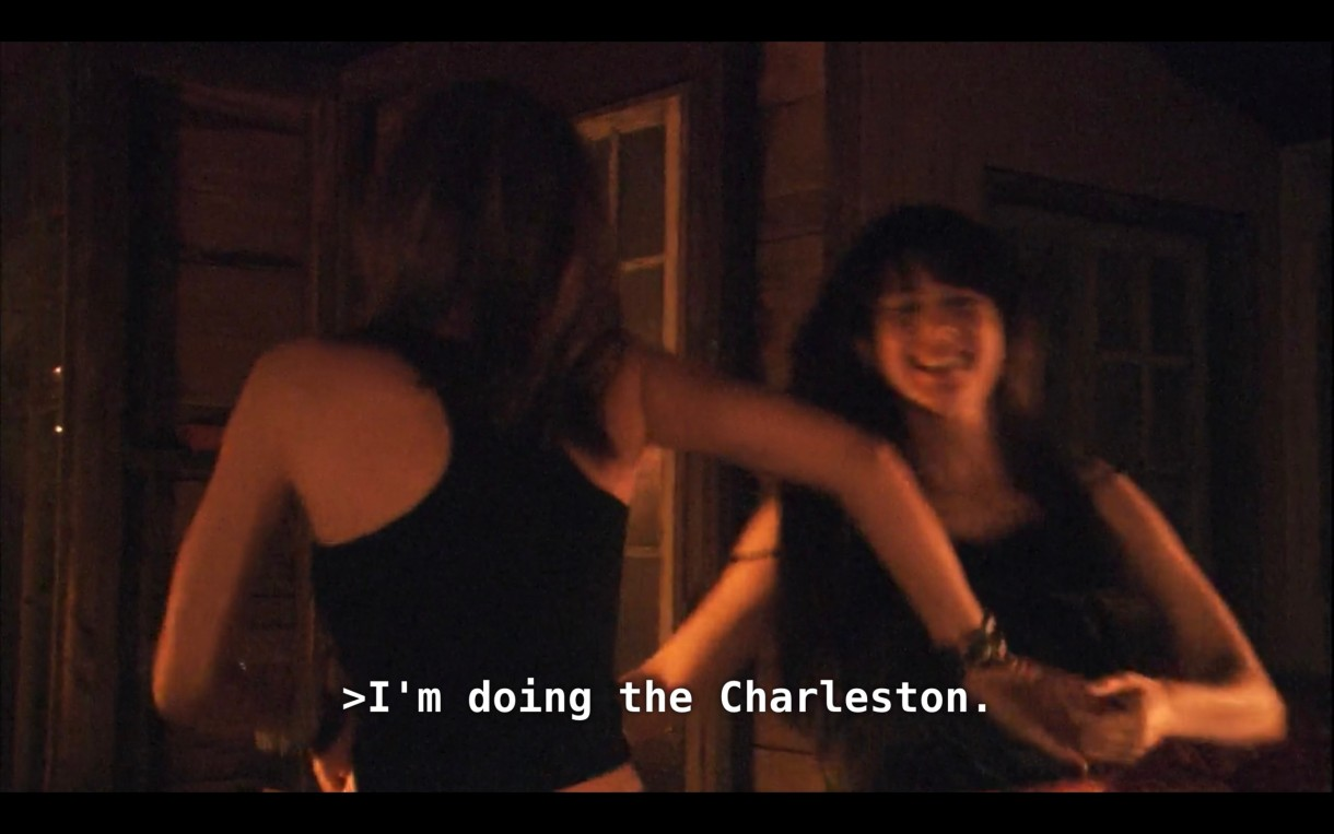 """Dana and Jenny (both wearing black tank tops) are holding hands and dancing together in a dimly lit room. Dana says, """"I'm doing the Charleston."""""""