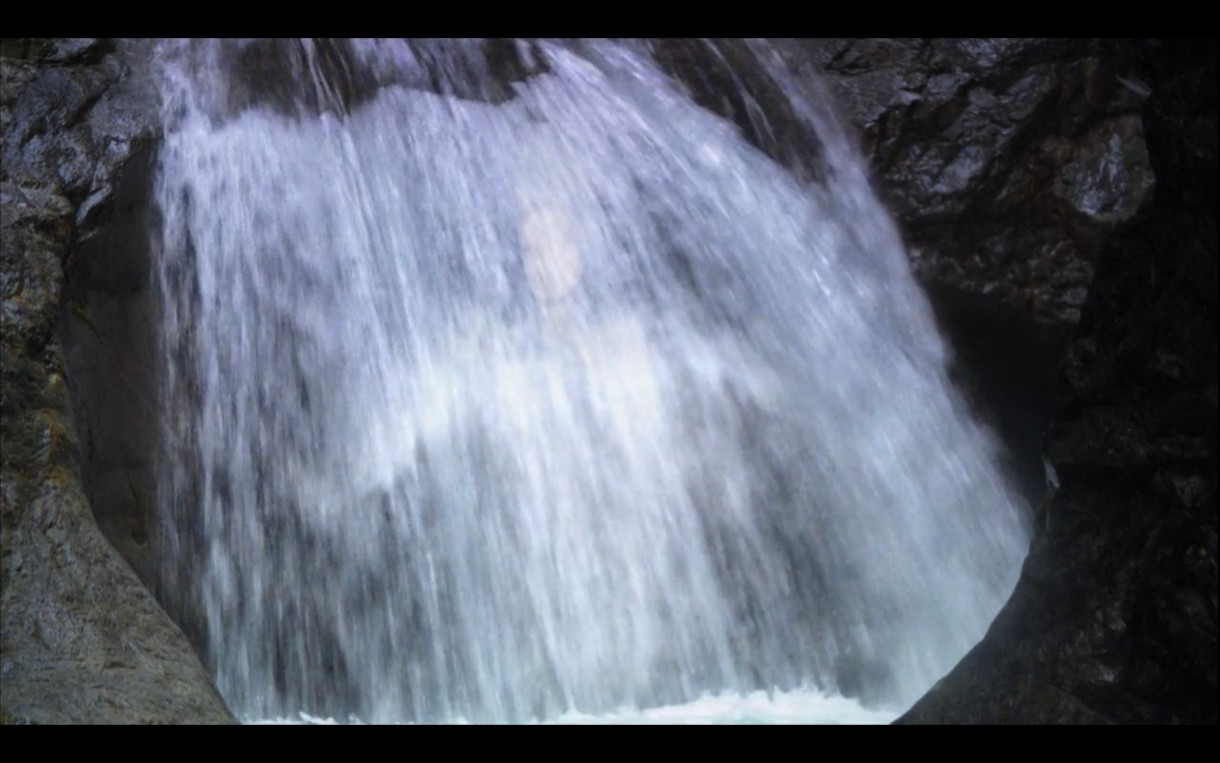 A serene waterfall. Ever so slightly Dana's body can be seen glimmering in the falling water.