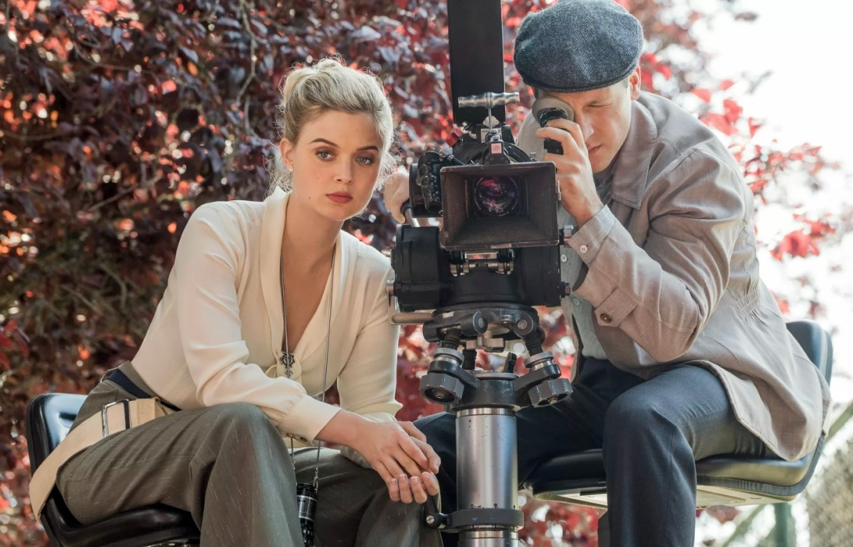 Image: A blonde white woman in a v-neck white silk shirt and grey pants is sitting behind a camera with a white man, who is looking through the camera. This scene appears to take place in the 40s or 50s.