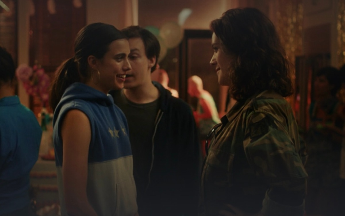 A screenshot from Adam of two queer women talking at a party while Adam looks over their shoulders.