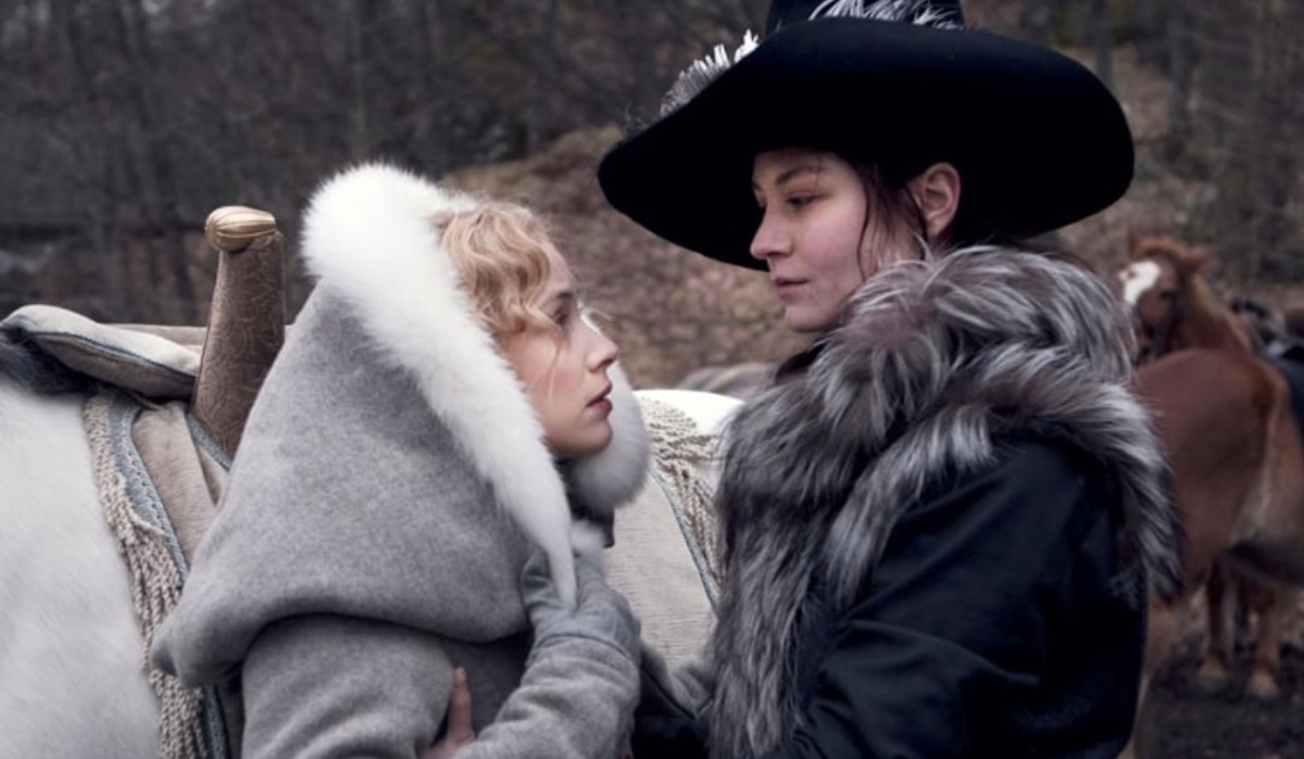 Image: two women wearing a lot of fur are staring at each other expressionless next to a horse. This is a lesbian movie available for streaming on Hulu.