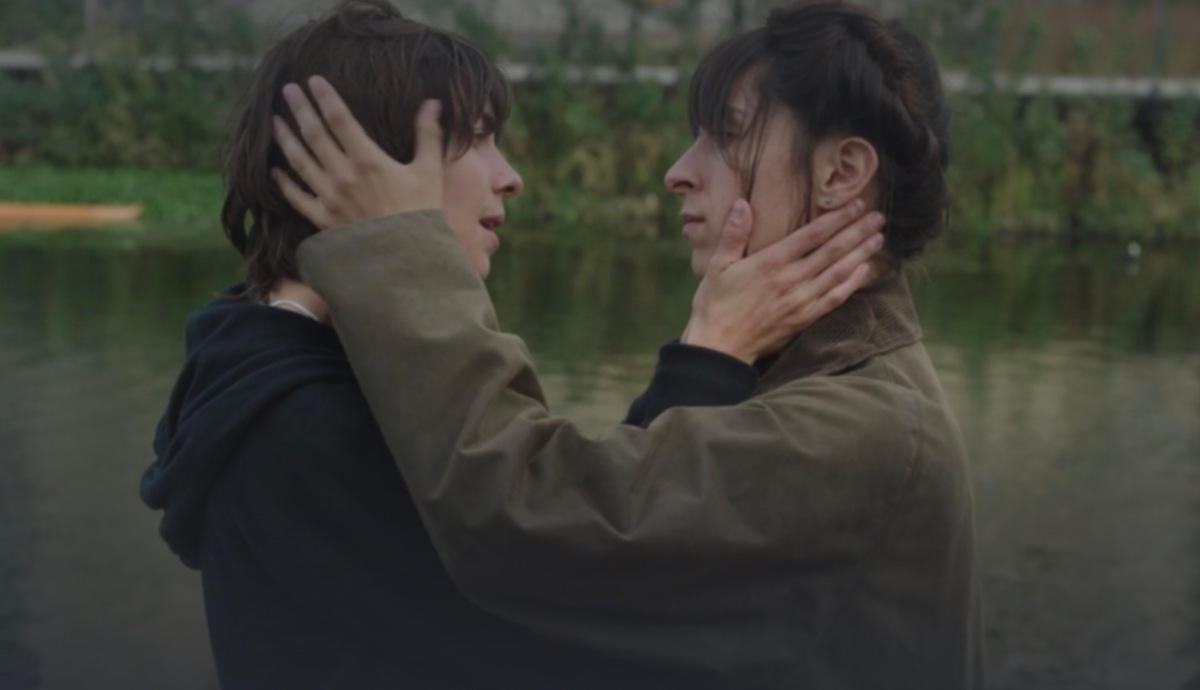 A screenshot of two lesbians holding each other by the faces near a pond.