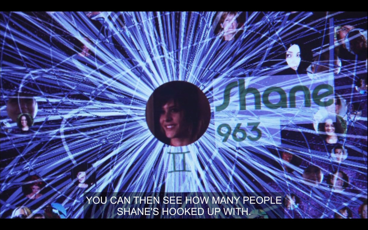 """A visual of Shane's place on OurChart. Alice, off screen, says, """"You can then see how many people Shane's hooked up with."""" On the screen it says that Shane has hooked up with 963 people."""