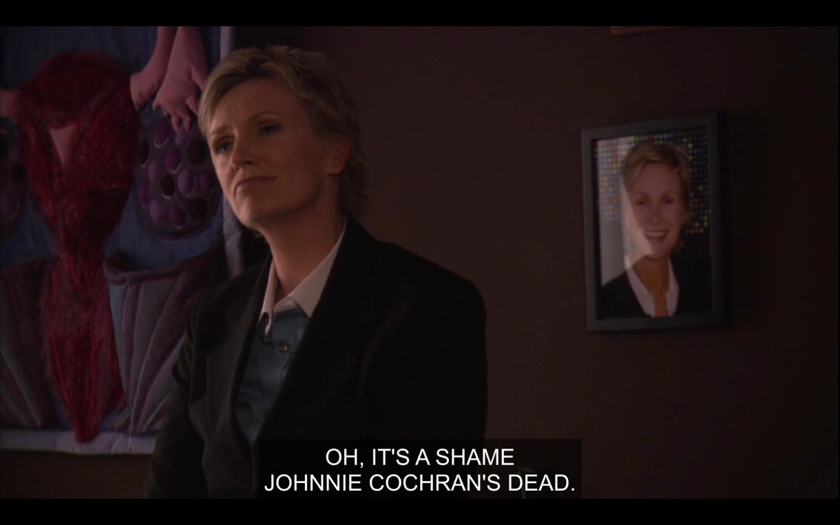 """Joyce Wyshnia says """"It's a shame Johnnie Cochran's Dead."""" Behind her is a big tapestry of a vulva, and also a headshot of herself"""