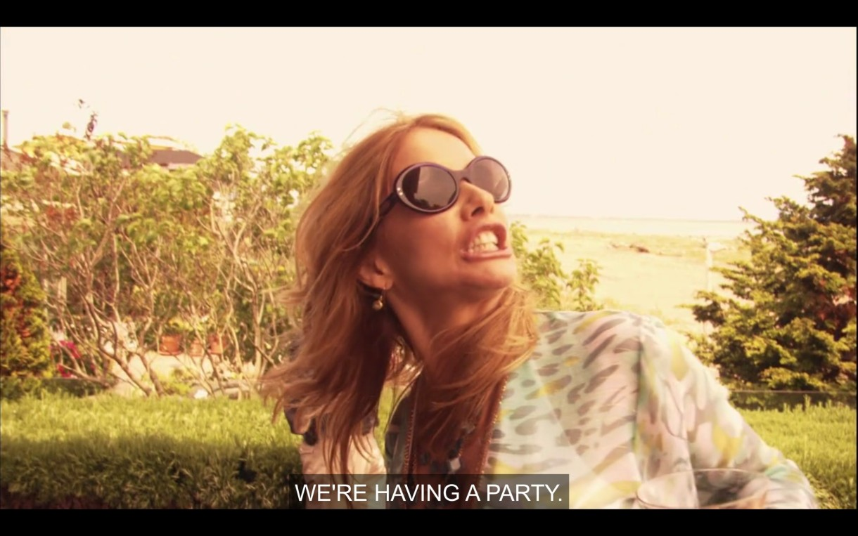 """Cherie screams """"WE'RE HAVING A PARTY."""" She's wearing sunglasses, the beach is behind her, she looks bananas"""