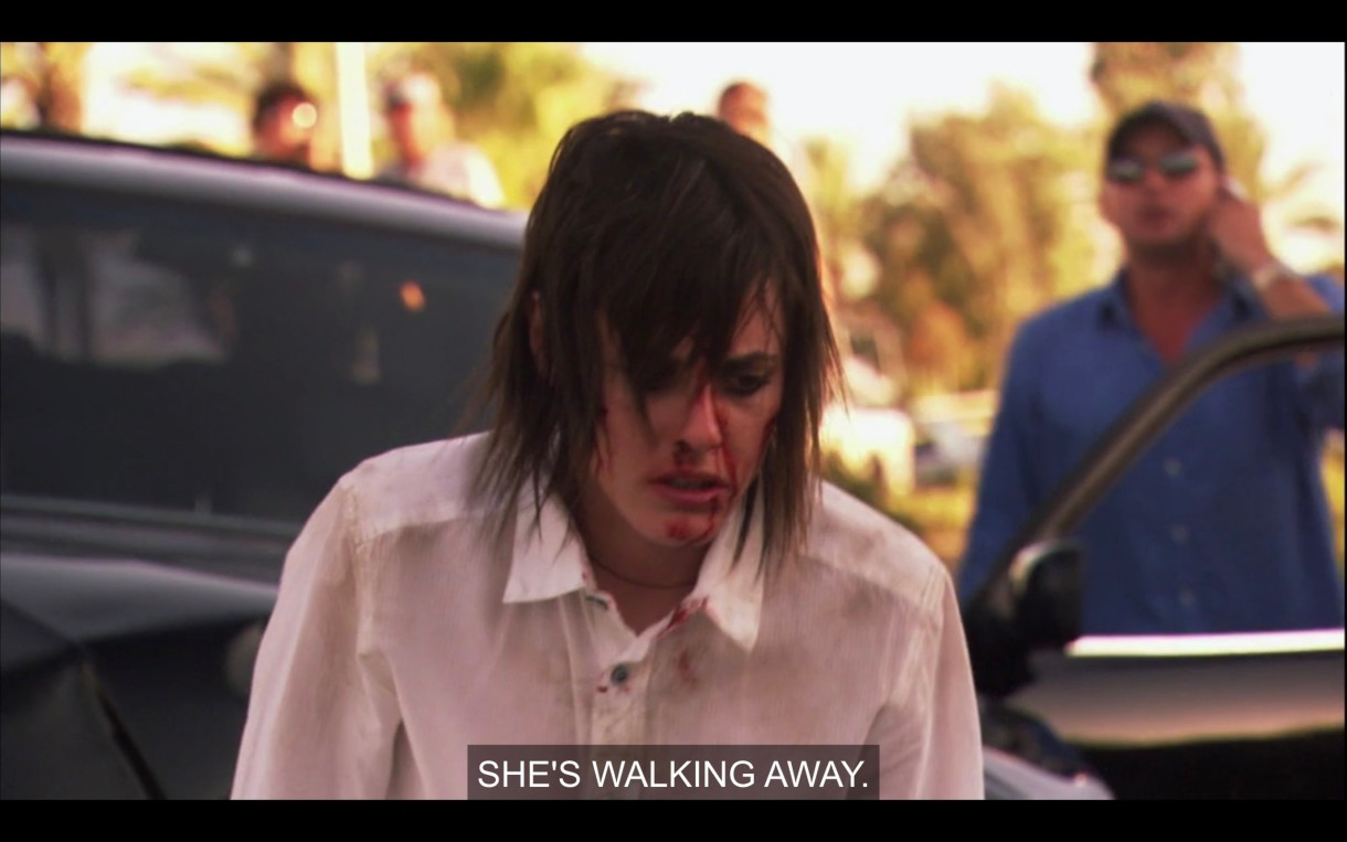 """Shane, in a white button-up shirt with blood all over her face and her hair all over her face is walking away from a car crashed she caused. in the background a dude is on the phone saying """"She's walking away."""""""