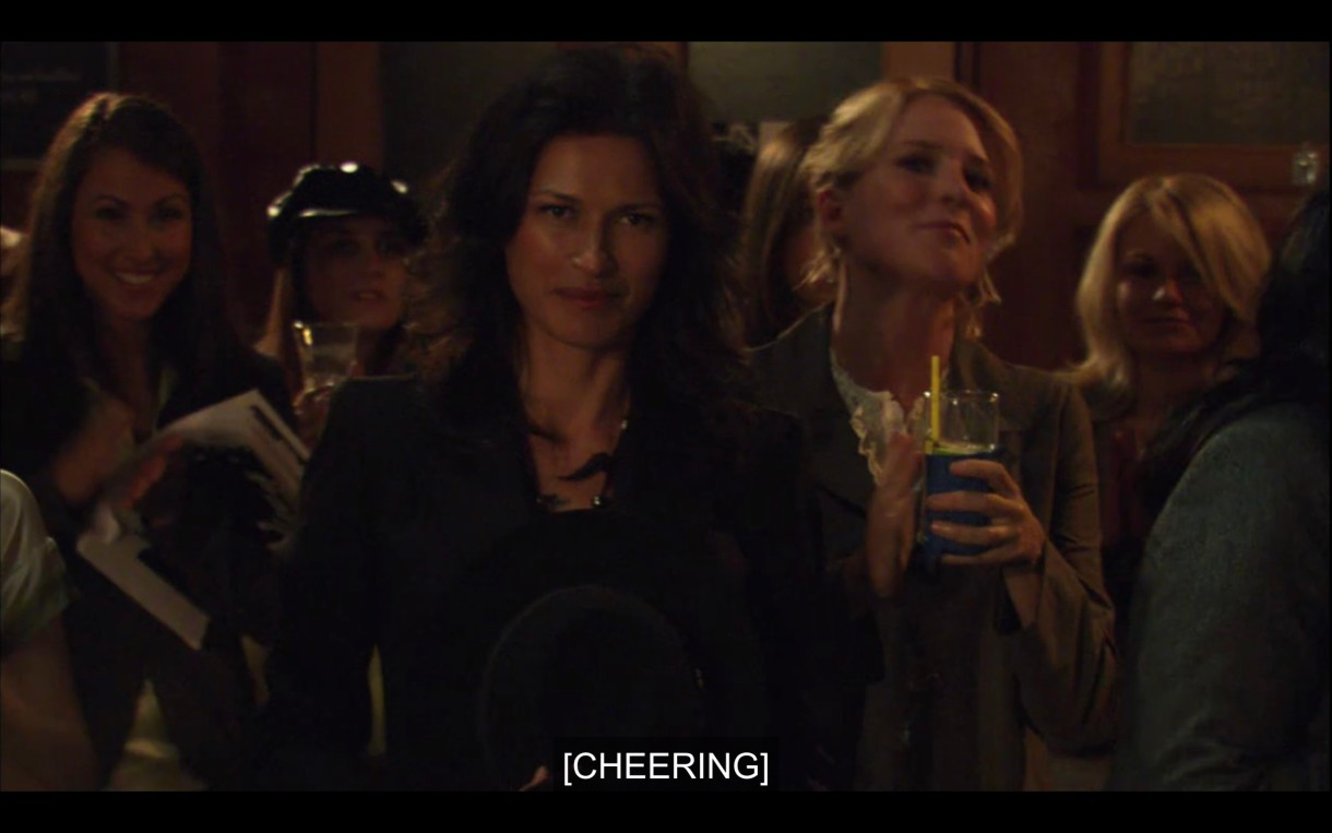 """Marina shows up at Jenny's reading. Tina is standing behind her holding a drink. Subtitles read, """"[Cheering]"""""""