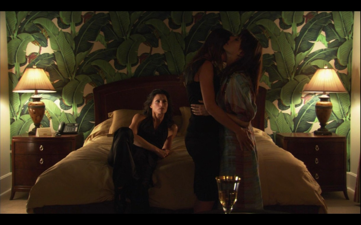 In a hotel room with wallpaper that looks like a forest. Marina is lying on the bed. Dim lighting. Claude and Jenny are standing up, making out.