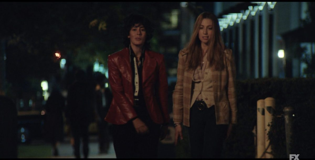 Image: it's nighttime and Jules, a photographer, is wearing a read leather jacket and walking with Brenda Feigen, an activist in a plaid blazer. Jules is played by Roberta Colonidrez, who is VERy hot.