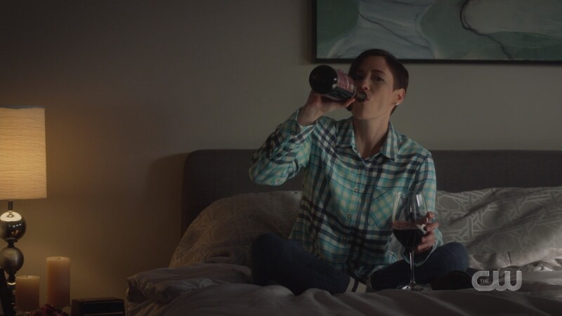 Alex holds a glass of wine but drinks from the bottle
