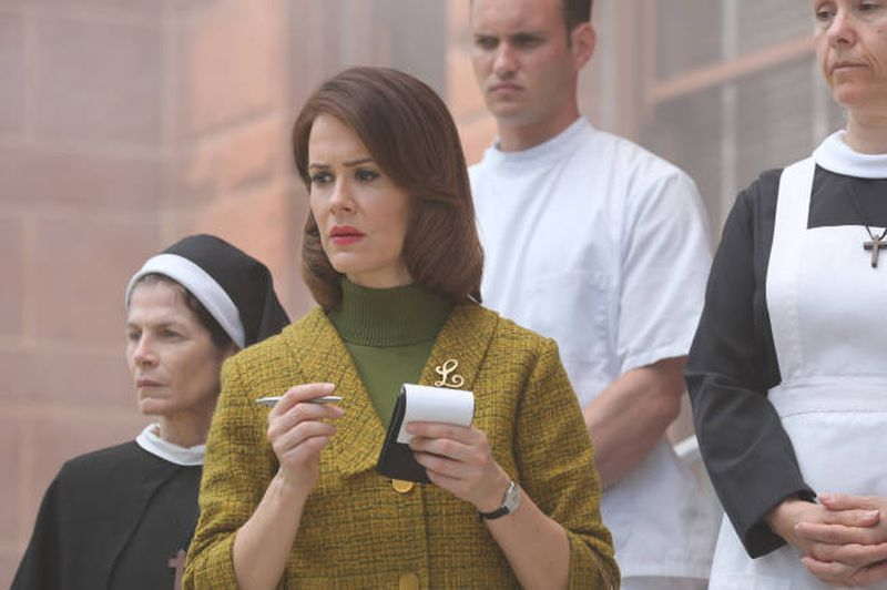 "Image: Lana Winters, played by Sarah Paulson, is a reporter. She is white with brown hair and red lips, a green turtleneck and a mustard-colored blazer with a gold pin reading ""L."" She is holding a reporters notebook and a pencil. Behind her stand two nuns, as well as a man in all white. You can see one of the nuns full faces, but the other two figures are only partially visible. Lana looks confused and concerned."